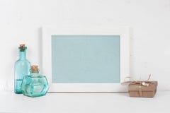 Пустые деревянные белые рамка, бутылки синего стекла и подарочная коробка Стоковое фото RF