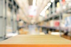 Пустые деревянные столешница или полка на предпосылке склада blurr Стоковые Фотографии RF