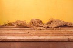 Пустые деревянные таблица и дерюга палубы над желтой предпосылкой стены для монтажа продукта Стоковое фото RF