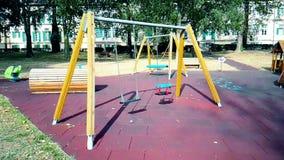 Пустые качания с цепями пошатывая на спортивной площадке для ребенка, двинутой от ветра, медленного сток-видео