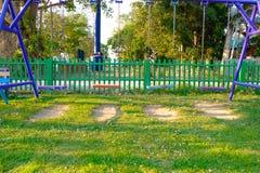 Пустые качания цепи и металла в поле травы спортивной площадки и луга Стоковая Фотография RF