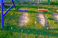Пустые качания цепи и металла в поле травы спортивной площадки и луга Стоковые Изображения