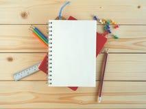 Пустые книга и канцелярские принадлежности на деревянном столе Стоковая Фотография RF