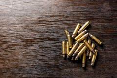 Пустые кожухи на темноте, деревянный стол пули стоковые фотографии rf