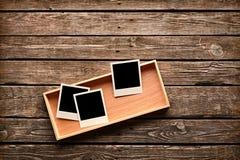 Пустые немедленные рамки фото на деревянной коробке Стоковые Изображения