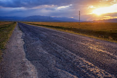 Пустые дорога, облака и заход солнца Стоковые Фотографии RF