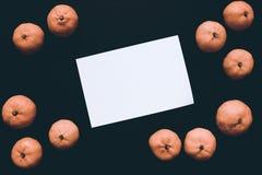 Пустые открытка и tangerines на черной таблице Апельсины и пустой год сбора винограда карточки тонизировали фото Стоковое Изображение RF