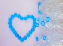 Пустые пластичные бутылки воды для рециркулируют с формой сердца от крышки бутылки Стоковые Фотографии RF