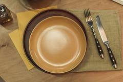 Пустые плиты, столовый прибор и салфетки на деревянной поверхности Стоковое Изображение
