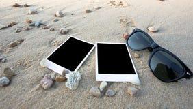 Пустые поляроидные печати фото и стекло солнца на песке моря Стоковое Изображение RF