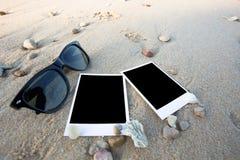 Пустые поляроидные печати фото и стекло солнца на песке моря Стоковое Изображение