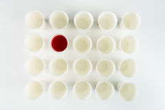 Пустые пластичные чашки и одно с красной краской Стоковое Изображение