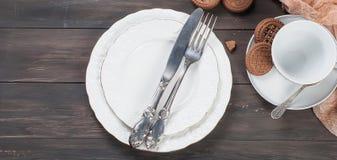 Пустые плиты, вилка, нож и чашка на деревянном столе Стоковая Фотография