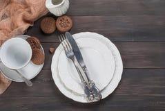 Пустые плиты, вилка, нож и чашка на деревянном столе Стоковое Изображение RF