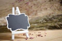 Пустые рамка и стойка доски на деревянной предпосылке Стоковая Фотография RF