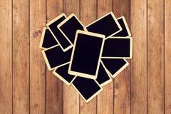Пустые ретро немедленные фото в форме сердца на деревянном столе для фотоальбома конструируют Стоковая Фотография RF