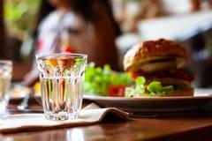 Пустые стекла коктеиля на таблице с гамбургером Стоковое Фото