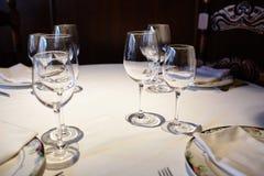 Пустые стекла в ресторане на белой скатерти Тень, коричневая предпосылка и высекаенные стулья Стоковые Изображения
