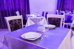 Пустые стекла и блюда установили в внутренний новый роскошный ресторан с покрытыми таблицами Стоковое фото RF