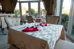 Пустые стекла и блюда установили в внутренний новый роскошный ресторан с покрытыми таблицами Стоковое Фото
