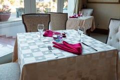 Пустые стекла и блюда установили в внутренний новый роскошный ресторан с покрытыми таблицами Стоковое Изображение RF