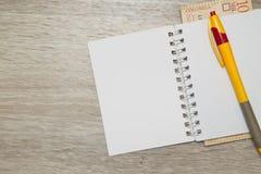 Пустые страница и ручка тетради с колумбийскими песо на деревянной таблице офиса Стоковое Изображение RF