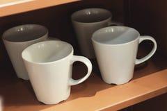 Пустые чашки кофе вися на деревянных полках Стоковые Изображения