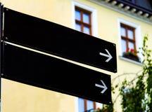 Пустые черные дорожные знаки или пустые дорожные знаки показывая направление против здания стоковое фото