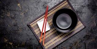 Пустые японские блюда Черный керамический шар для китайских лапш или тайские лож супа на половике bamkuk Белое saucepot для соево стоковые фотографии rf