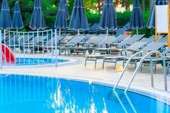 Пустые loungers солнца вокруг бассейна Стоковая Фотография RF
