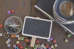 пустые signage, компас и камера на деревянной предпосылке Стоковые Фотографии RF