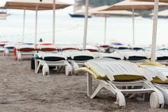 Пустые sunbeds на песчаном пляже Стоковая Фотография