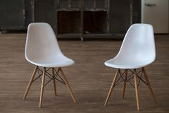 2 пустых белых деревянных footstools около деревянного стола в интерьере просторной квартиры с деревянным полом стоковое изображение