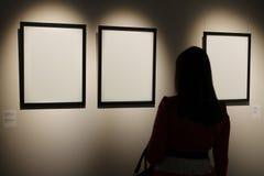 3 пустых белых рамки холста висят на стене с светлый светить Стоковая Фотография