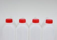 4 пустых канистры белой пластмассы с красными крышками Стоковое Изображение RF