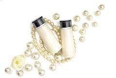 2 пустых косметических бутылки лежа на жемчугах Стоковое фото RF