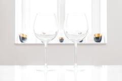 2 пустых красных бокала на белой таблице с белыми предпосылкой и окном Стоковые Изображения