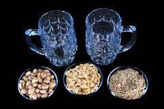 2 пустых кружки пива с фисташками, арахисами и семенами подсолнуха Стоковая Фотография