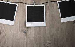 3 пустых немедленных фото вися на веревке для белья на деревянной предпосылке, концепции искусства Стоковое Изображение