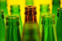 10 пустых пивных бутылок на желтой предпосылке Стоковые Фотографии RF