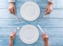 2 пустых плиты и столового прибора в человеческих руках Стоковая Фотография RF