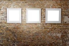 3 пустых рамки на светлой кирпичной стене Плакаты пустого пространства или рамка искусства ждать быть заполненным Квадратная черн Стоковая Фотография RF