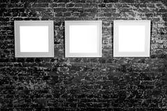 3 пустых рамки на черной кирпичной стене Плакаты пустого пространства или рамка искусства ждать быть заполненным Квадратная черна Стоковые Изображения