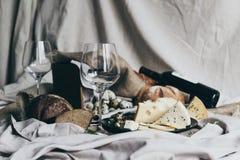 2 пустых рюмки стоят готовыми быть заполненным при сухое красное вино лежа позади Свежий хлеб, голубой сыр, masdaam Стоковые Фотографии RF
