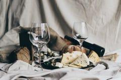 2 пустых рюмки стоят готовыми быть заполненным при сухое красное вино лежа позади Свежий хлеб, голубой сыр, masdaam Стоковое Изображение RF