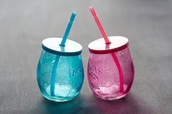 2 пустых стекла, сделанного из голубого и красного стекла с соломами Стоковые Фотографии RF