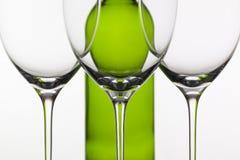 3 пустых стекла вина и зеленой бутылки Стоковые Изображения