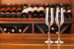 2 пустых стекла в предпосылке с бутылками вина Стоковые Фотографии RF