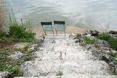 2 пустых стуль на озере подпирают на дне старых скалистых лестниц с большим взглядом позади Стоковые Изображения RF