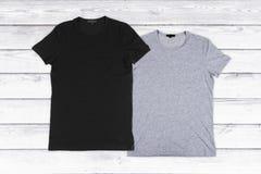 2 пустых футболки на белой деревянной предпосылке Стоковое фото RF